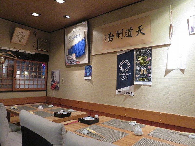 「鮨dining松雪」のテーブル席と、桐生順平選手のサイン入りジャンパー