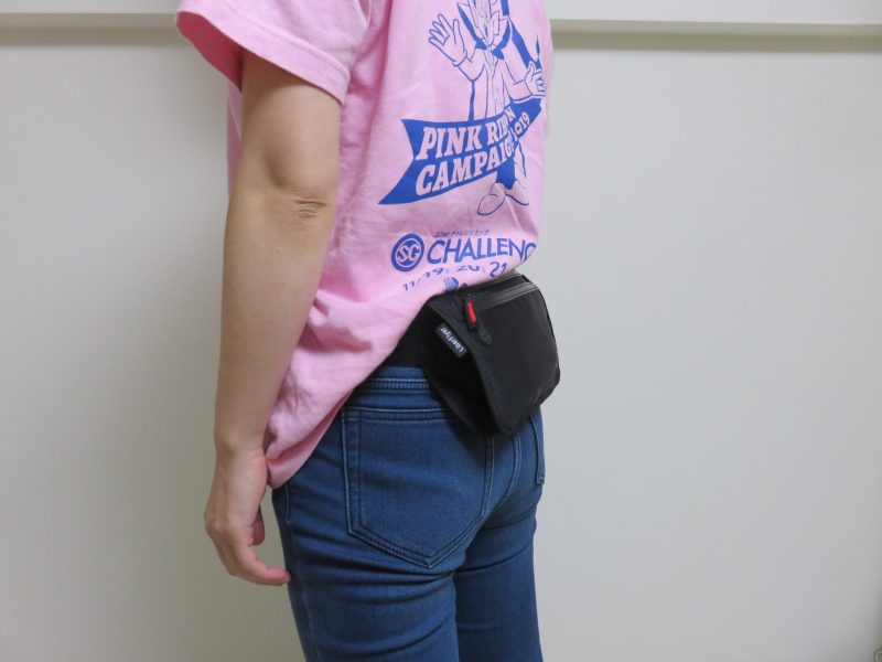 セキュリティポーチの「セキュリポラージサイズ」を女性が服の上の背中側につけた様子
