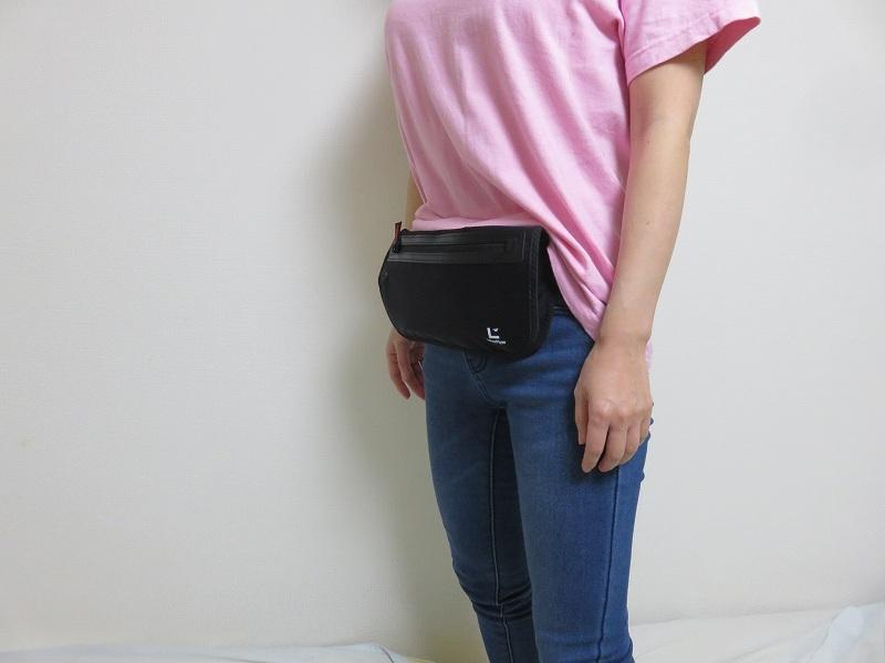 セキュリティポーチの「セキュリポラージサイズ」を女性が服の上のお腹側につけた様子