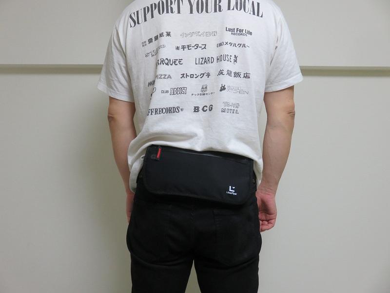 セキュリティポーチの「セキュリポラージサイズ」を男性が服の上の背中側につけた様子