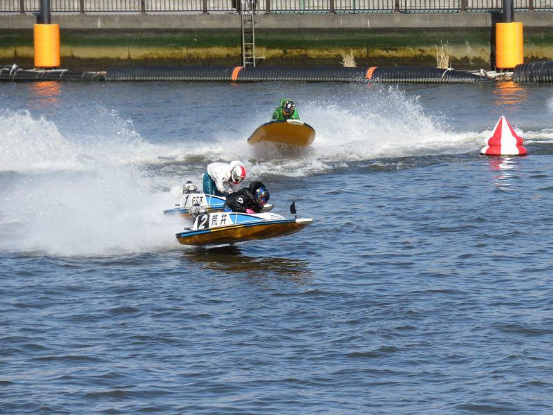 首都高速の下の道から見た江戸川競艇場の競争水面1マーク側を、選手たちが旋回するようす